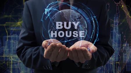 mülkiyet : Male hands activate a conceptual holographic text Buy house. Businessman in a suit with a hologram of planet Earth on a background of a futuristic wireframe city Stok Video