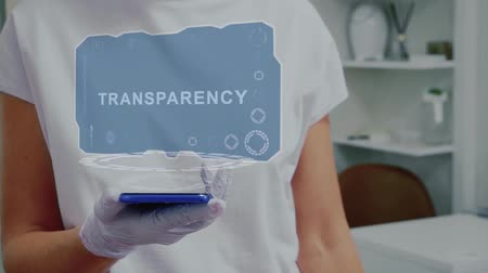 clareza : Doctor in medical glove against background of doctors office with HUD hologram text Transparency. Hand holds futuristic holographic gadget. Medical technology concept of the future