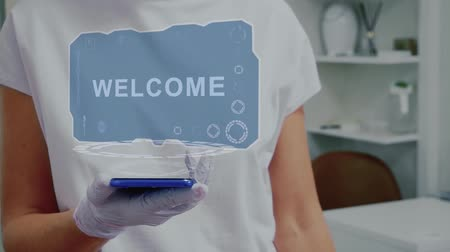 seçme : Doctor in medical glove against background of doctors office with HUD hologram text Welcome. Hand holds futuristic holographic gadget. Medical technology concept of the future Stok Video