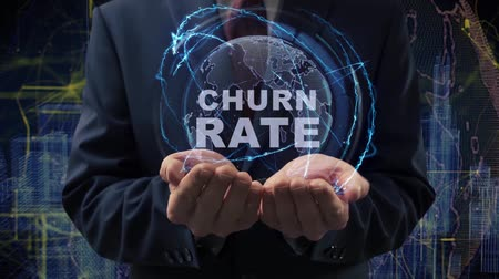 functioneel : Male hands activate a conceptual holographic text Churn rate. Businessman in a suit with a hologram of planet Earth on a background of a futuristic wireframe city
