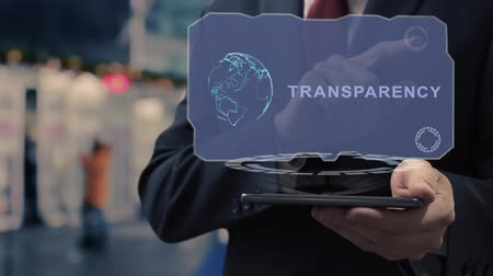 clareza : Unrecognizable businessman uses hologram on smartphone with text Transparency. Man in shirt and jacket with holographic screen on background of entrance to the airport or train station Stock Footage