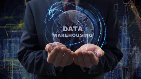 digital code : Male hands activate a conceptual holographic text Data Warehousing. Businessman in a suit with a hologram of planet Earth on a background of a futuristic wireframe city Stock Footage