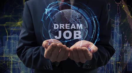 seçme : Male hands activate a conceptual holographic text Dream job. Businessman in a suit with a hologram of planet Earth on a background of a futuristic wireframe city