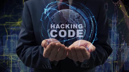 digital code : Male hands activate a conceptual holographic text Hacking code. Businessman in a suit with a hologram of planet Earth on a background of a futuristic wireframe city