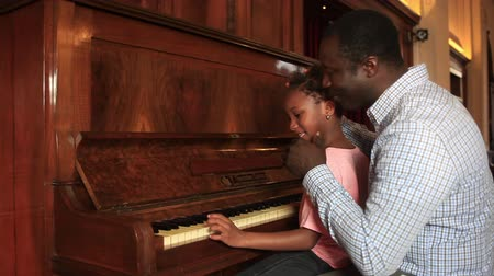 black : Father teaching piano to his daugther Stock Footage