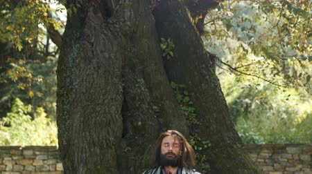 A white man with a beard sitting in meditation with crossed legs under the tree