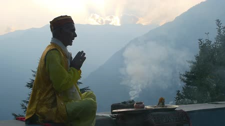 A Hindu old man in yellow offering special spiritual prayer to god