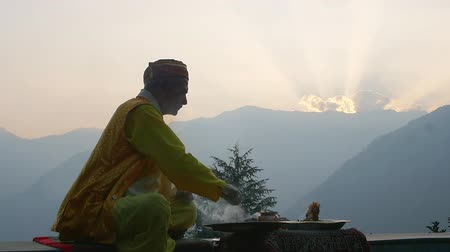 thali : A Hindu old man in yellow offering special spiritual prayer to god
