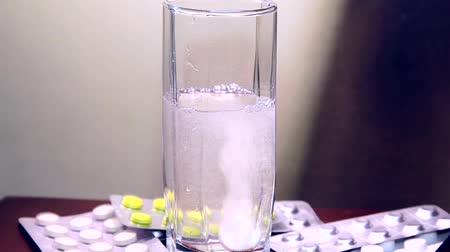 oldódó : Drugs. Water poured into glass and falls aspirin tablet into Stock mozgókép