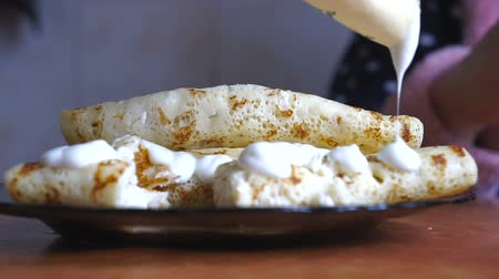 bolo de queijo : A Person eats cheese pancakes with sour cream with a knife and fork