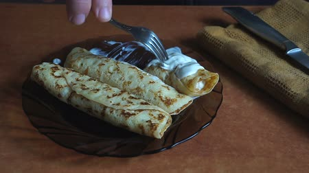 оладья : A Person eats cheese pancakes with sour cream with a knife and fork