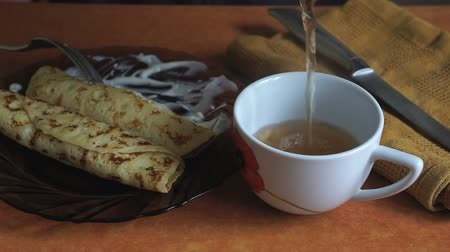 tvaroh : A Person eats cheese pancakes with sour cream and pour tea in the cup Dostupné videozáznamy