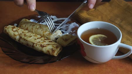 tvaroh : A Person eats cheese pancakes with sour cream with a knife and fork