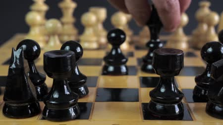 vintage : Panning shot of a chess board with a hand moving the chess pieces. Wideo