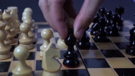 šachy : Panning shot of a chess board with a hand moving the chess pieces. Dostupné videozáznamy
