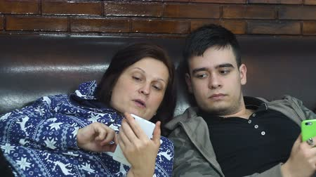 nurture : Mom and her son teenager, look at the smartphone touch the touch screen