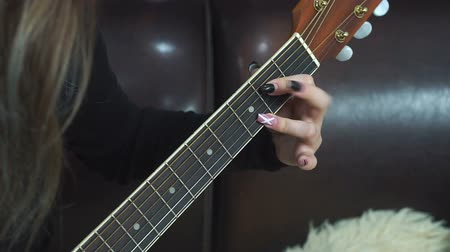 честный : Closeup of young womans hand, strumming the guitar