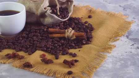 italian coffee : Coffee cup and coffee beans. A white cup of falling coffee on the table with roasted bean.