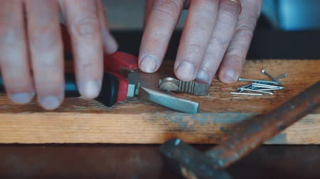 díszgomb : the craftsman pulls a nail from the plank