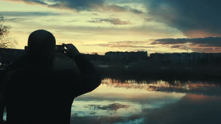 hayran olmak : Silhouette of man talking photo of sunset with cellphone