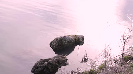 boulders : The Stone river bank. Glare the sun on the water. Stock Footage