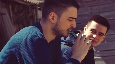 vaper : A boy smokes an electronic cigarette in the street Stock Footage