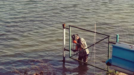 labour : welder working on a piece of metal, making fence, stand in the water Stock Footage