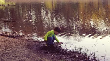 kamış : A child playing on the shore of thelake. Walks in the fresh air. A beautiful scenic place.