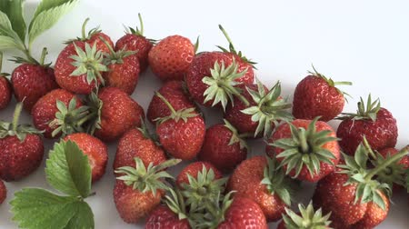 клубника : Group of fresh strawberries on white background. Dolly shot.