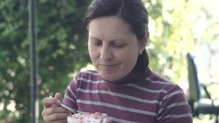 yoghurt : Young women eat dessert with strawberry.