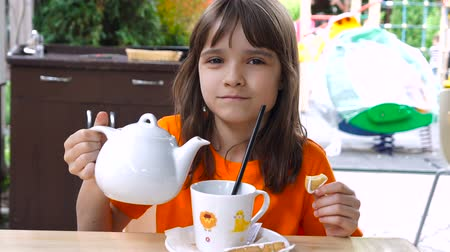 brew tea : Little girl pouring tea in the cup.