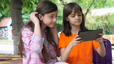 social life : Two Girls are Using Tablet Outdoors Sitting in the Park. Young Amazing Girls are Looking at the Screen of Electronic Gadget. Stock Footage