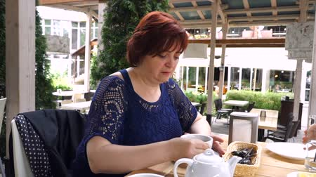 sentiment : Lady with a tea pot pouring tea in the cup on the wooden table in the cafe. Stock Footage