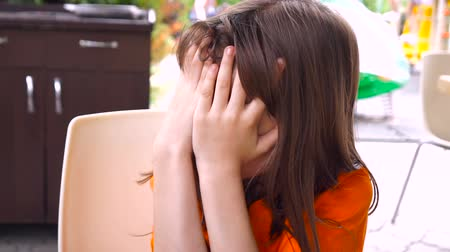 hides : Little girl covers her face with hands. Close up. Stock Footage