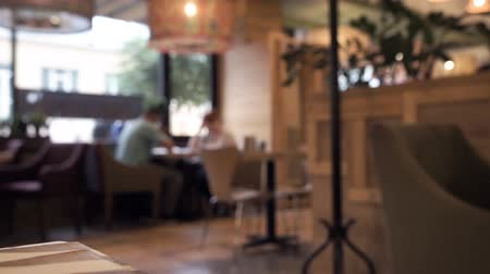 cena urbana : Blurred footage of cafe with people drinking coffee and tourists walking pass. Video with defocused effect.