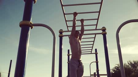 into the camera : Young athletic man doing warm-up before exercise and jogging Stock Footage