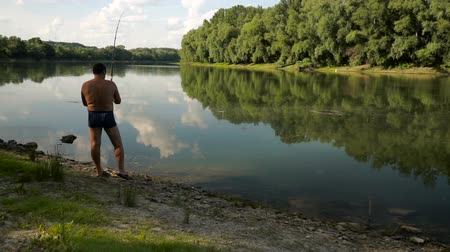 ужение : Fishing in river.A fisherman with a fishing rod on the river bank.