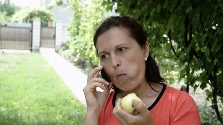 hívó : Close up of a mature beautiful happy woman talking on the phone holding an apple.