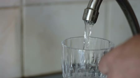 enchimento : Pouring a glass with drinking water from the kitchen tap Vídeos