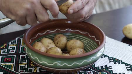 starch : Peeling Potatoes in the home kitchen. A man holding a knife and peel the potatoes and clean in a bowl. Cooking food at home. Stock Footage