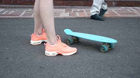 postura : skateboarding, leisure, extreme sport and people concept - teenage girl legs riding short modern cruiser skateboard on road Stock Footage