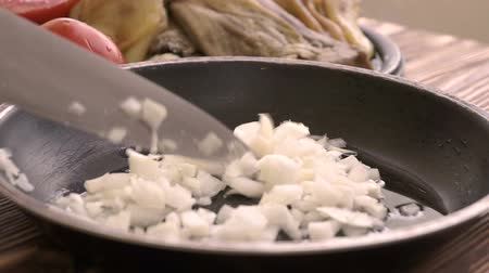 bıçaklar : Chef puts chopped onion to the frying pan with hot sunflower oil.