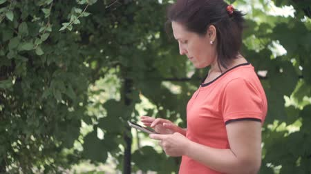 ignore : Young woman using smartphone outside at green trees nature background. Young woman on cell phone. Woman texting sms on her phone outside in park. Stock Footage