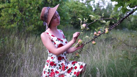 apple park : Beautiful blonde girl in hat and dress standing on the apple garden.