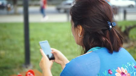 só : Portrait of an Amazing Woman with a Smartphone Outdoors. Pretty Brunette Using Her Mobile Phone with Touch Screen Standing in the Park Stock Footage