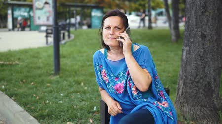 günışınları : Portrait of an Amazing Woman with a Smartphone Outdoors. Pretty Brunette Using Her Mobile Phone with Touch Screen Standing in the Park Stok Video