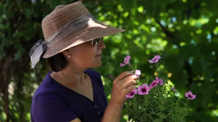 model s : Portrait of a woman in a hat admire flowers in the garden.