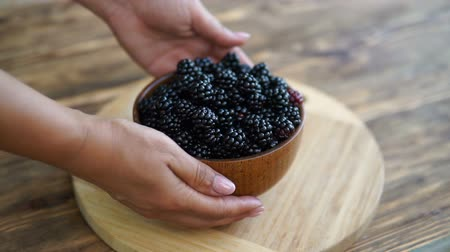 kertészeti : womans hand put a bowl with blackberries on a wooden table