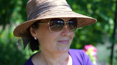 pronikavý : Close up of beautiful woman in hat and sunglasses looking at camera.