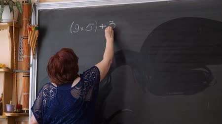 özel öğretmen : Teacher writing calculations on the blackboard in classroom Stok Video